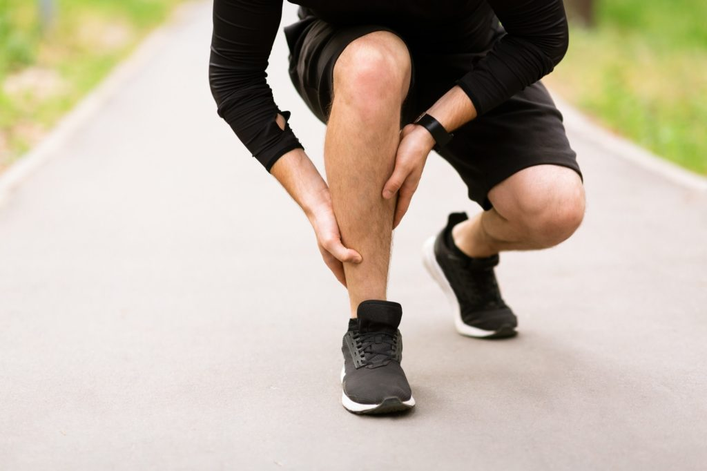 Calf sport muscle injury. Runner with pain in leg